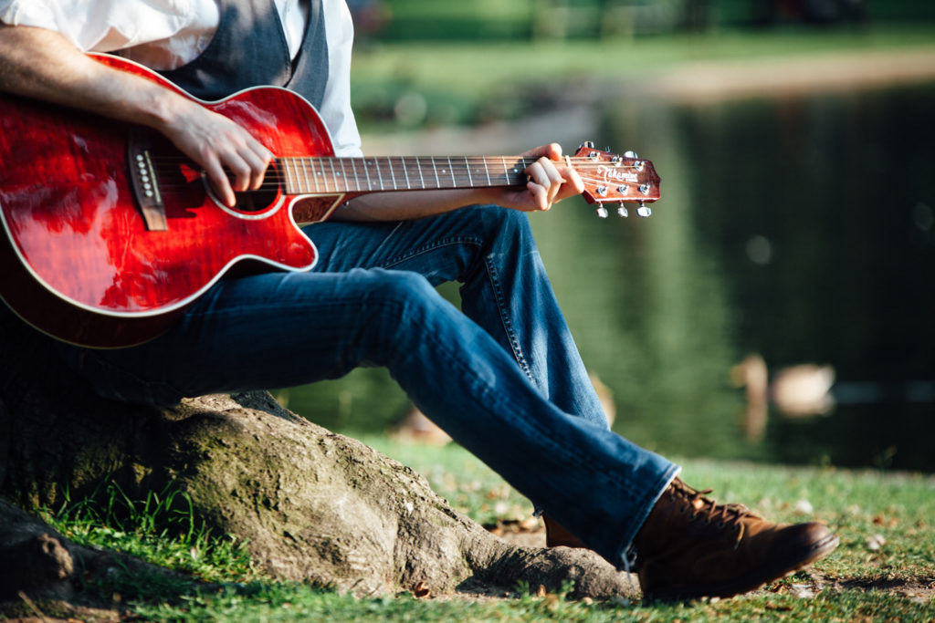 A guitarist playing their instrument near a pond.