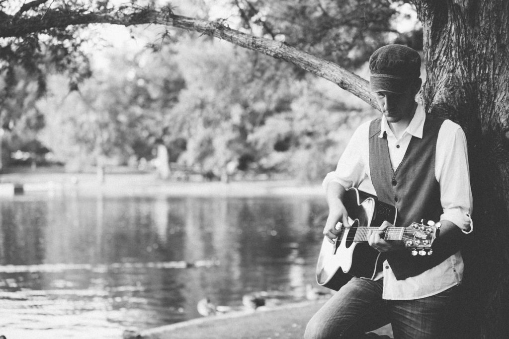 A man playing guitar by a pond.