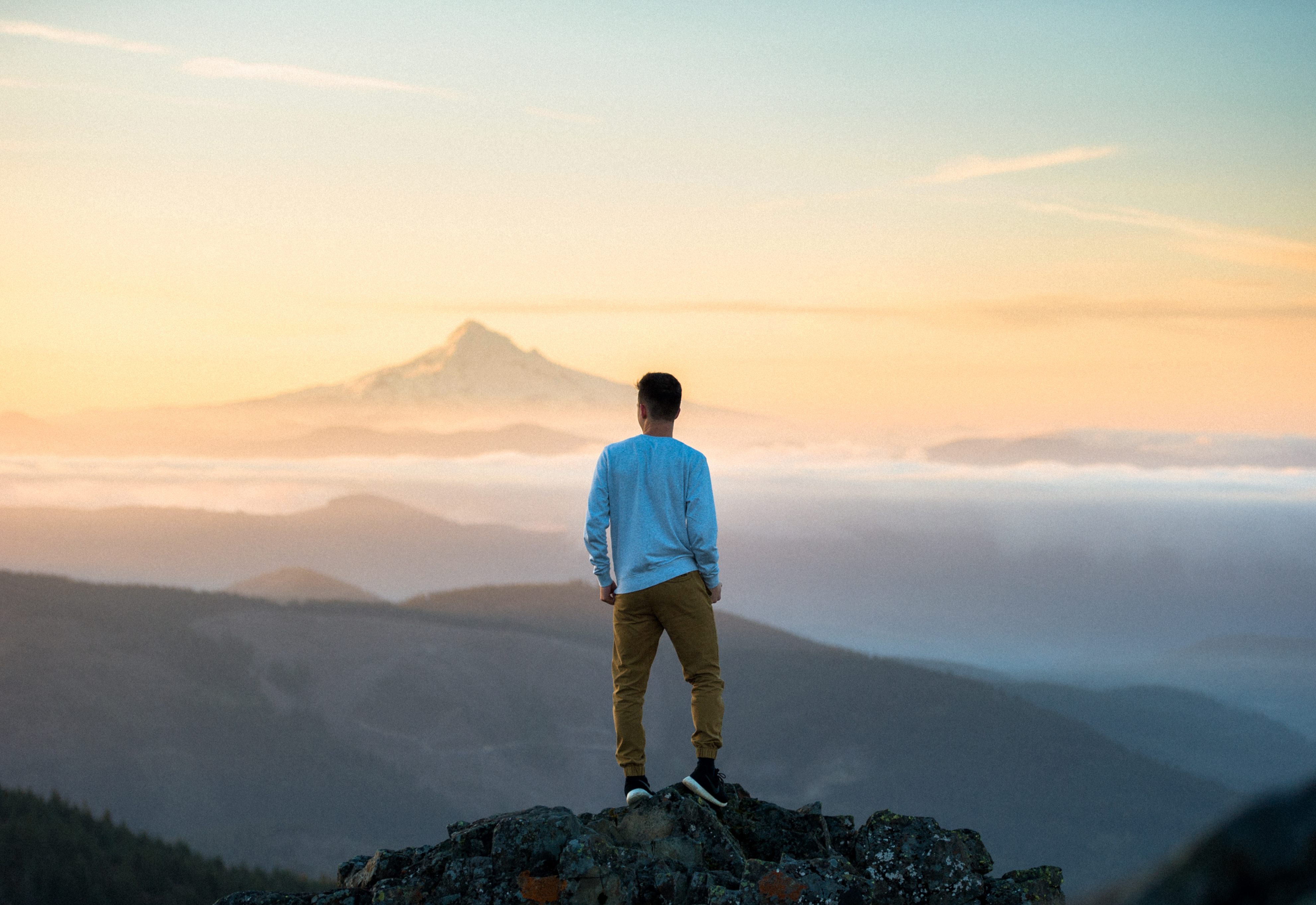 Man standing on top of a mountain observing the view and deep in thought about writing song lyrics.
