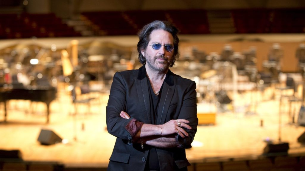 Kip Winger stands in front of a stage.