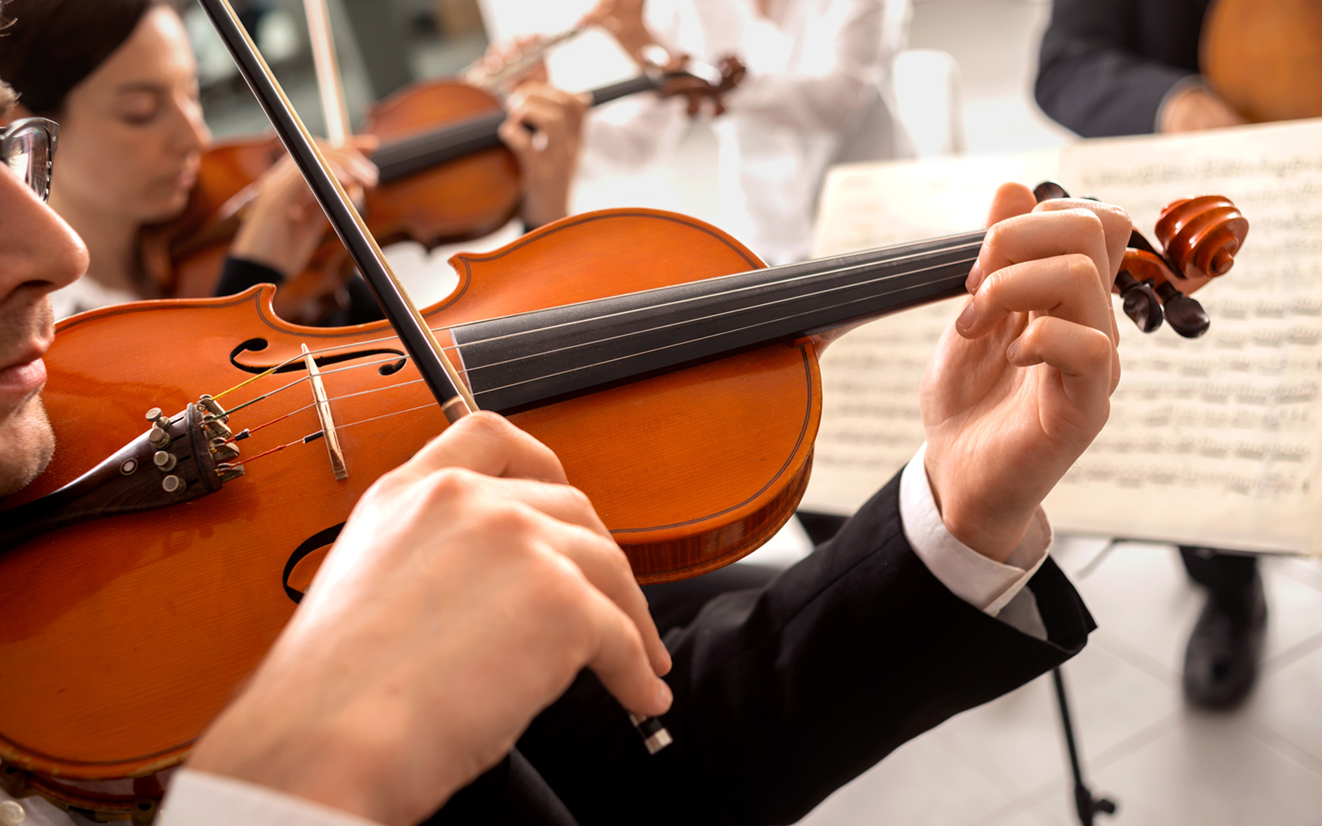 A violinist playing a music arrangement in an orchestra.