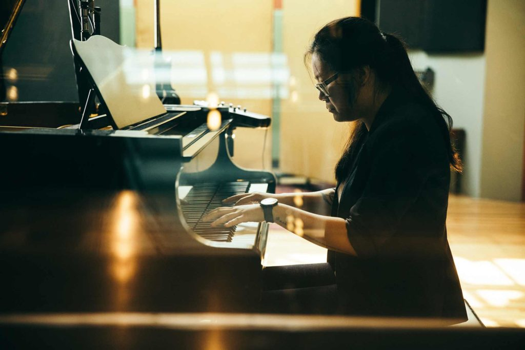 A woman playing piano using the music modes.