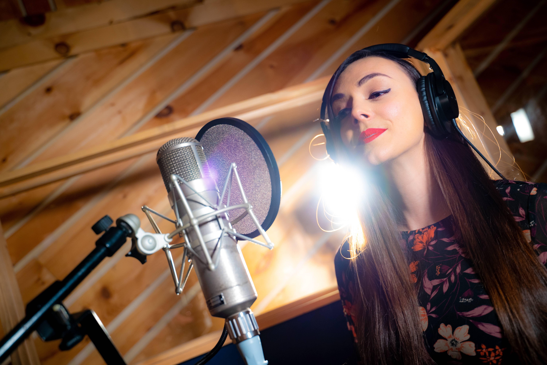 Berklee Online student Eirini Tornesaki singing into a microphone in a recording studio.