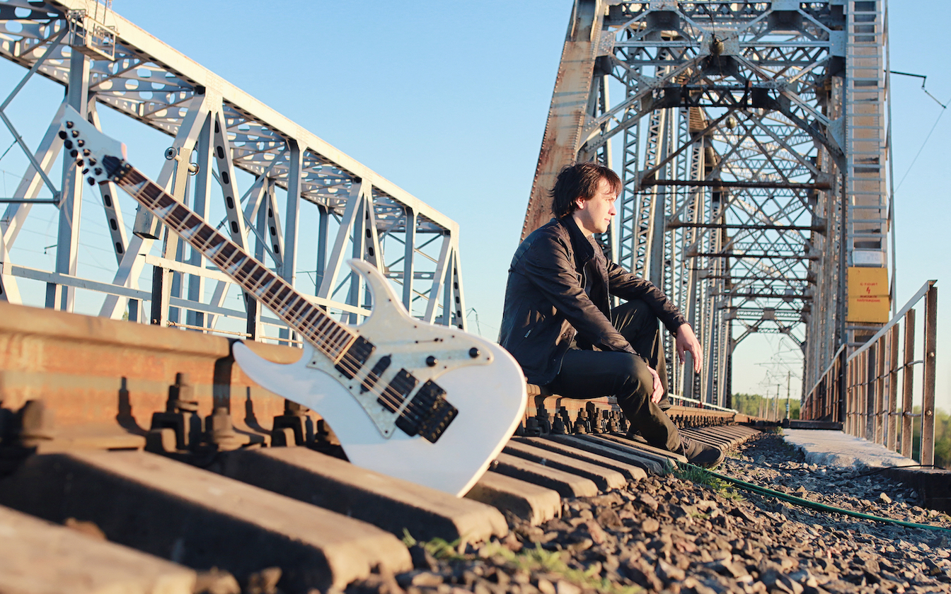A musician with their guitar sitting on a bridge.