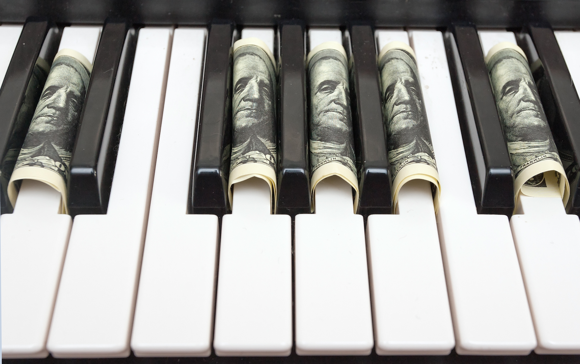A piano with 100 dollar bills tucked into the keys.
