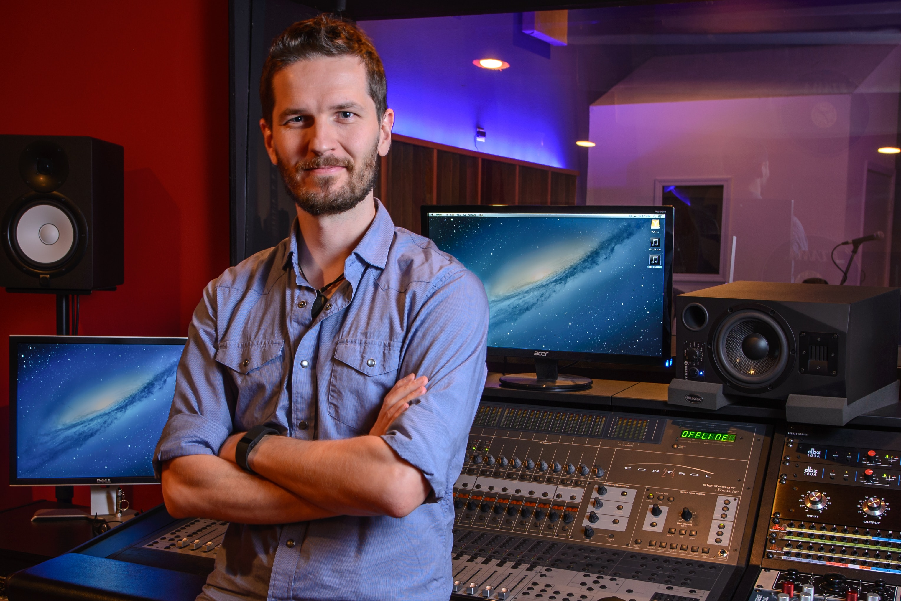 A recording engineer standing at the sound board in a recording studio.