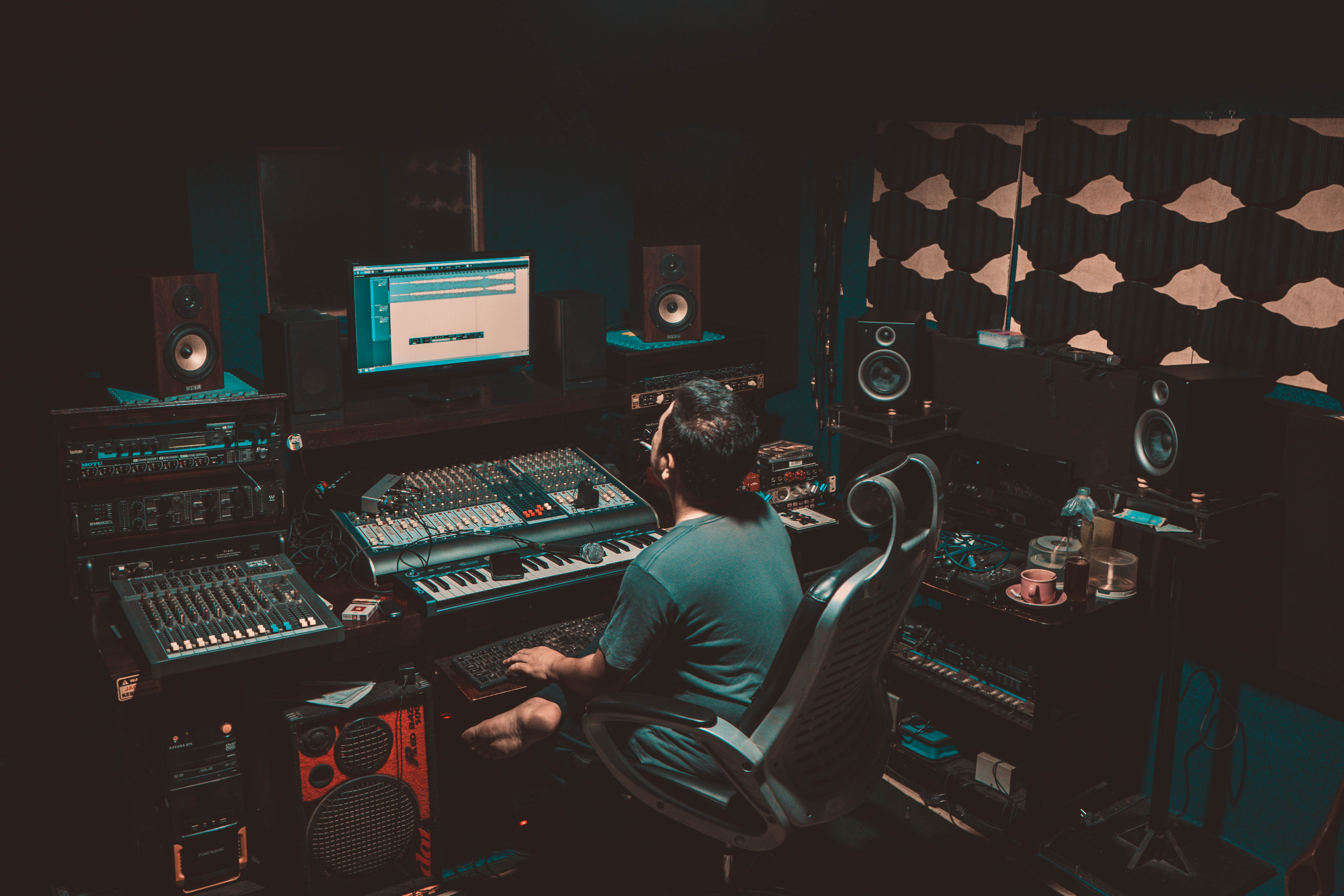 A music producer working on a sound board in a recording studio.