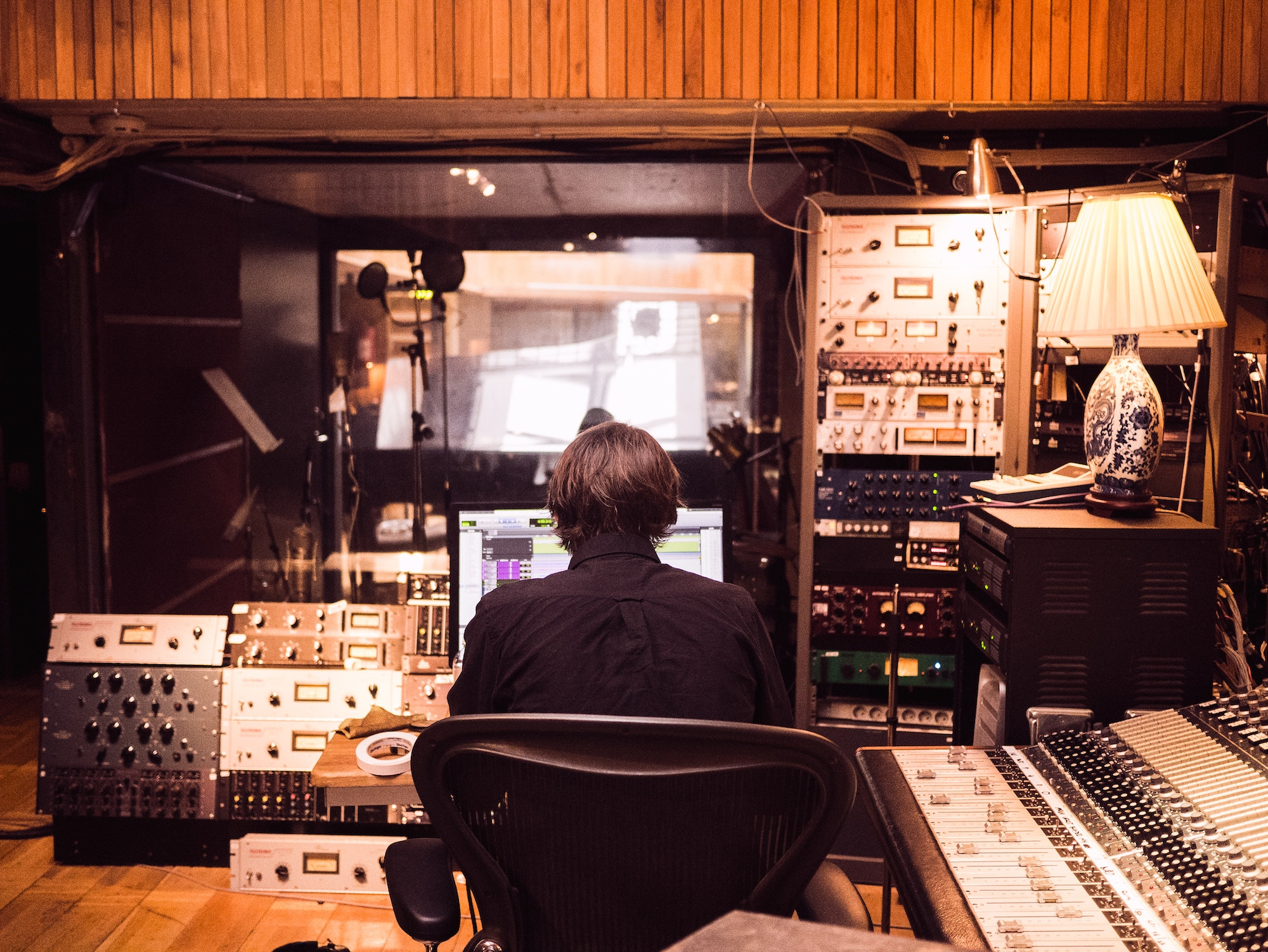 A musician working at a soundboard in a recording studio.