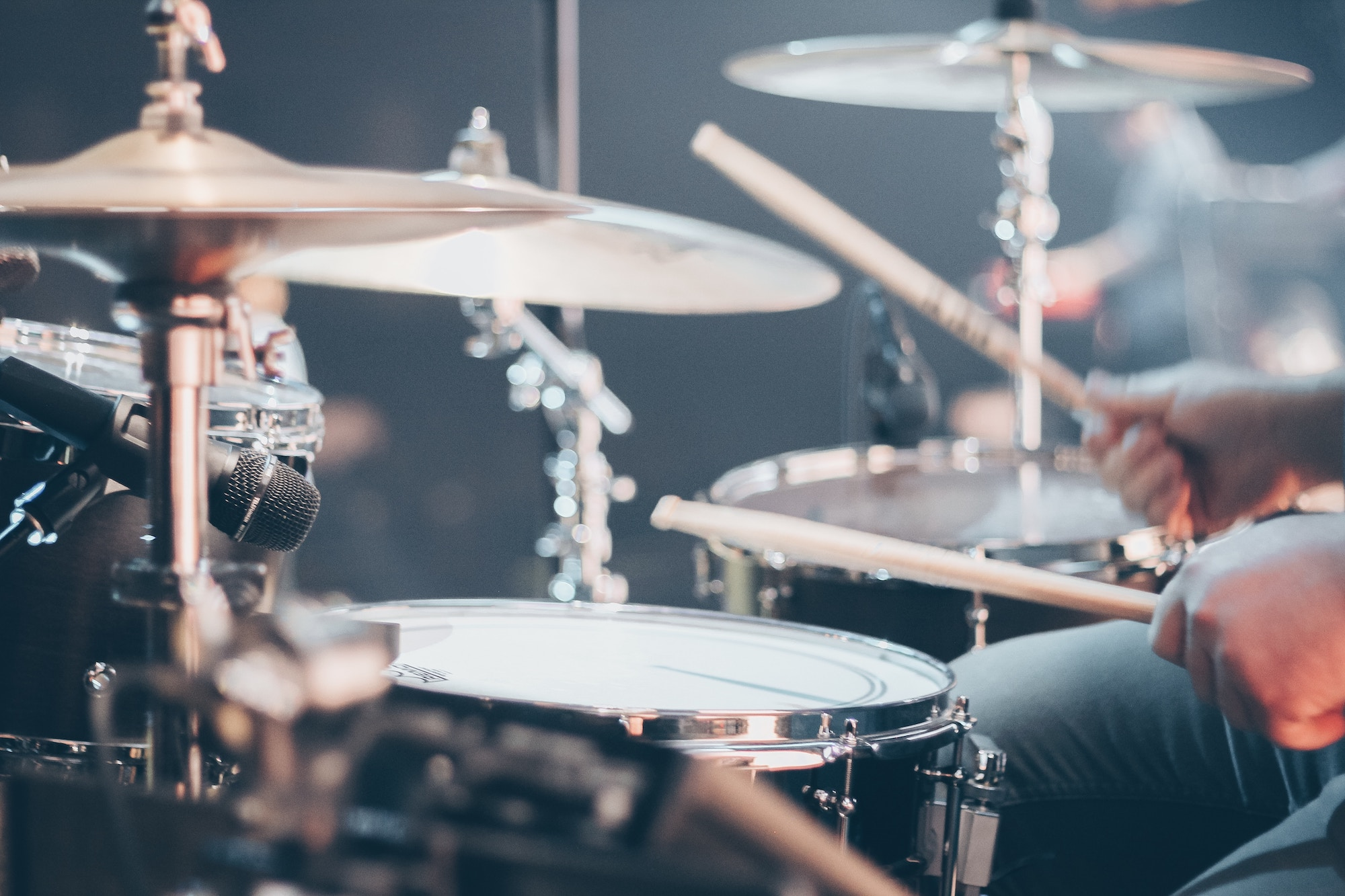 A drummer playing a drum kit.