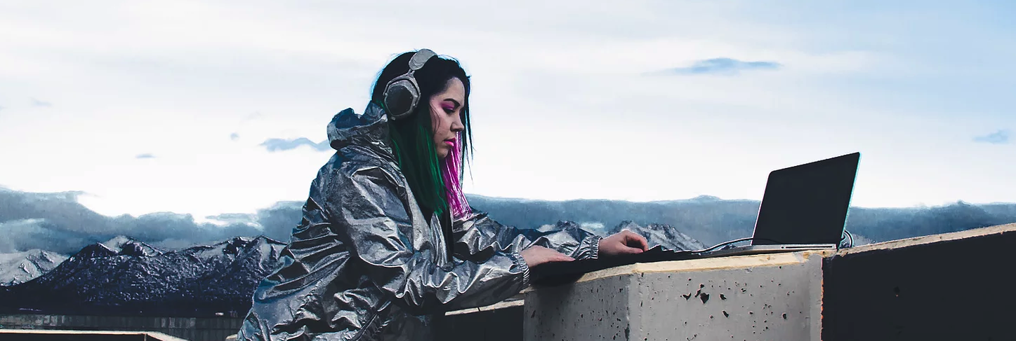 Rain Essex creating music on her laptap with mountains in the background.