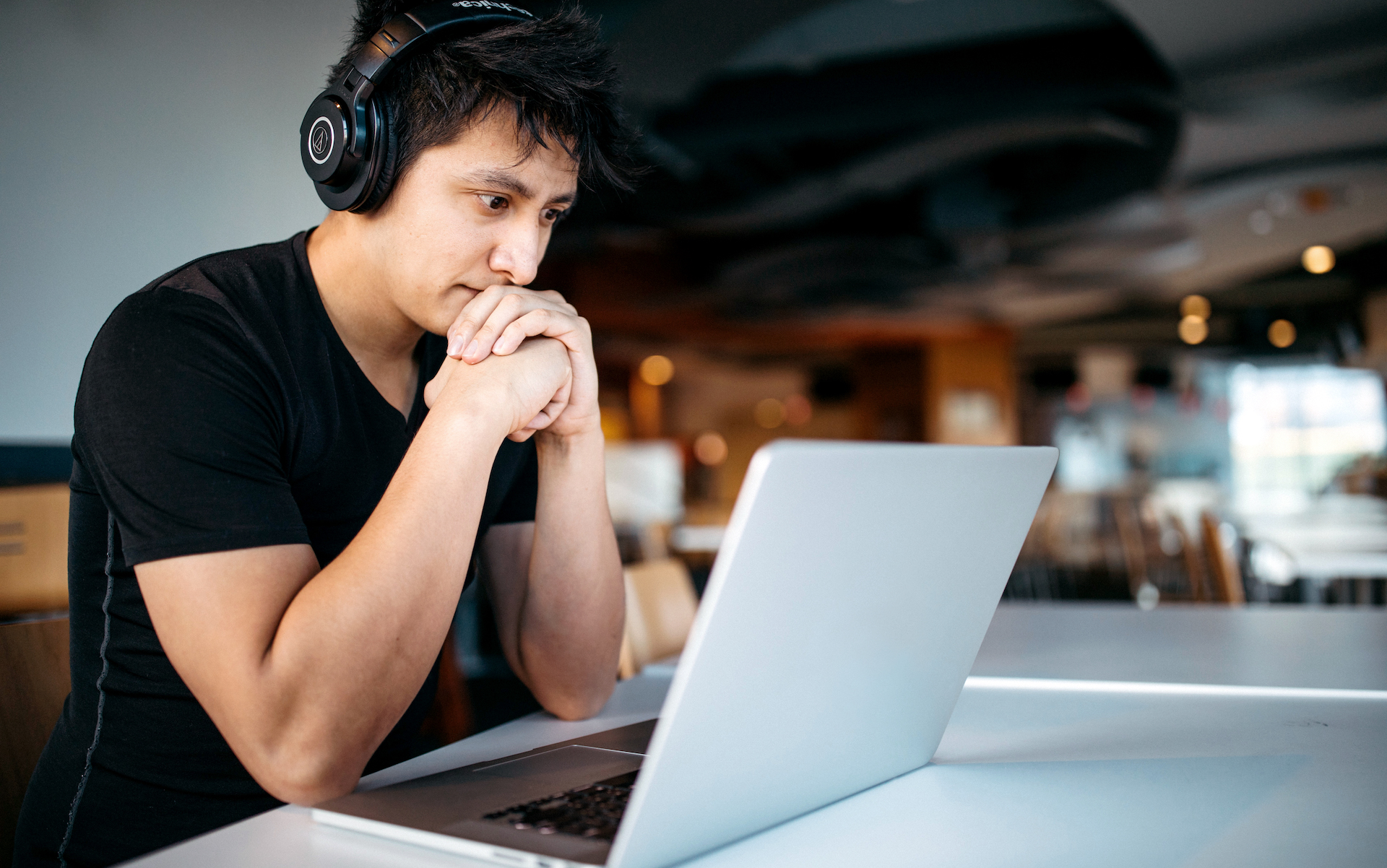 A musician sits at his computer creating his website.