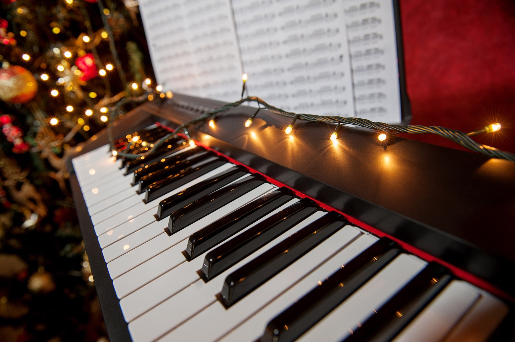 A piano with holiday lights running along the keys.