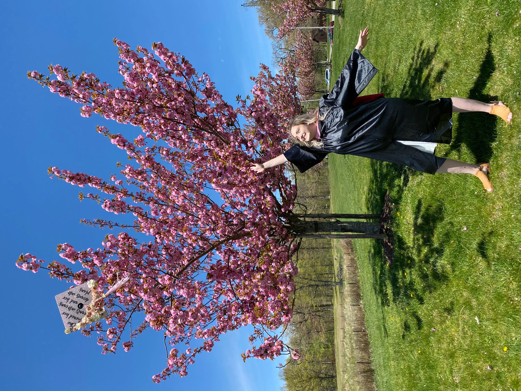 Berklee Online graduate Carrie Lane Pearlman throwing her cap in front of a blossoming tree.