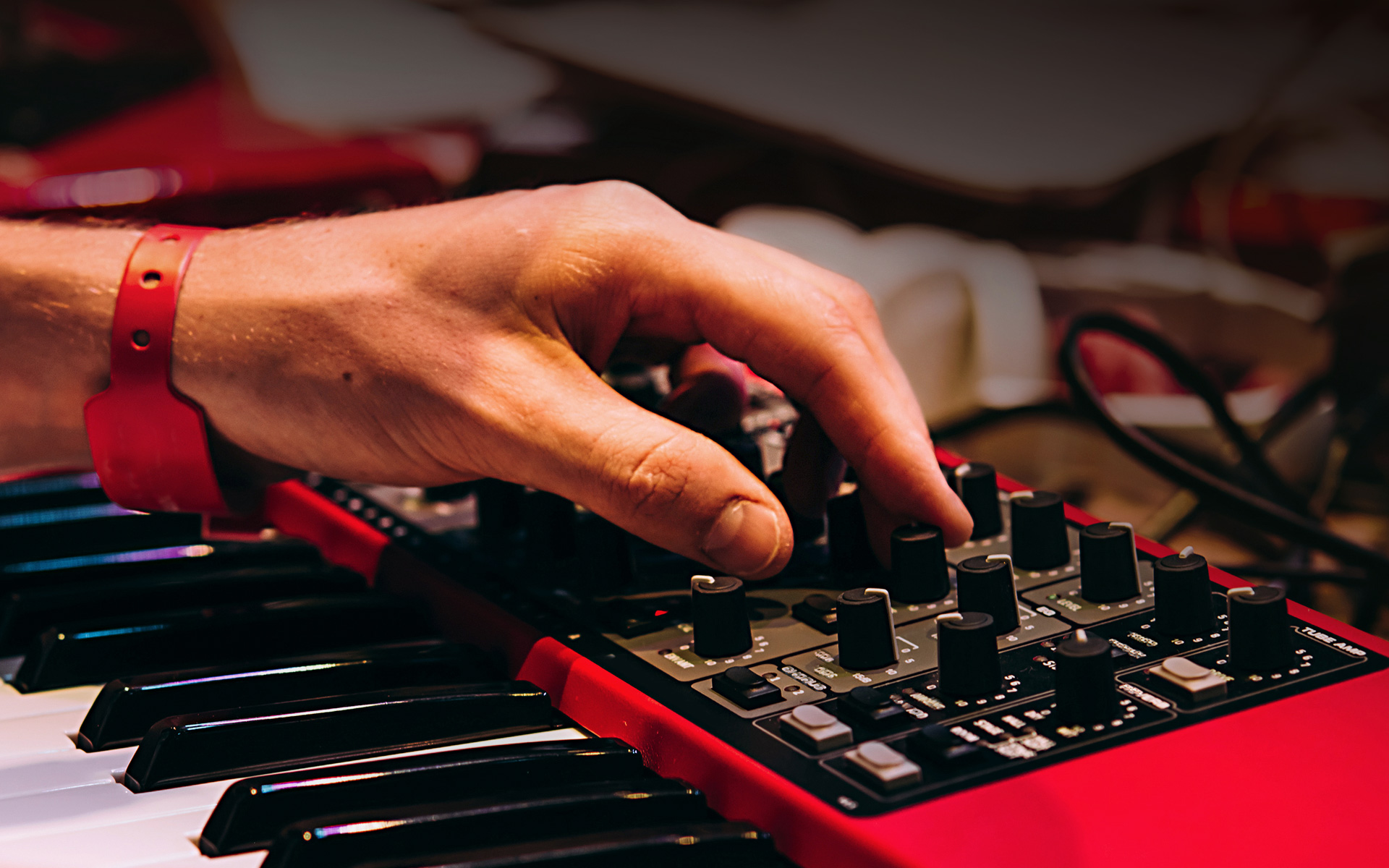 An electronic musician composing house music on a synthesizer.