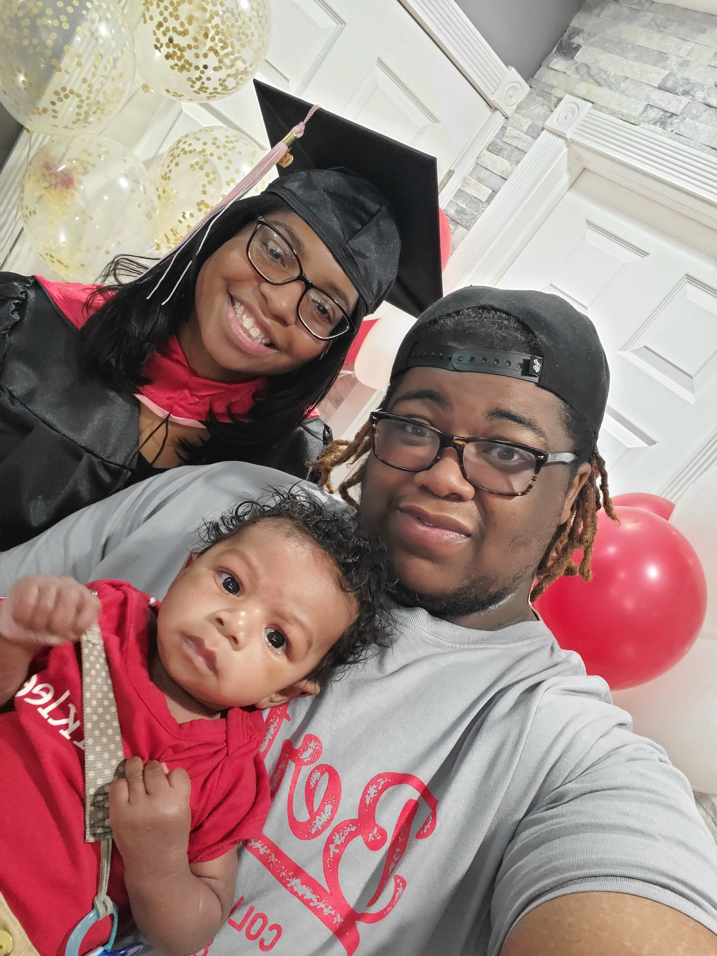 Gabrielle Davis, her husband, and newborn son take a selfie on graduation day.