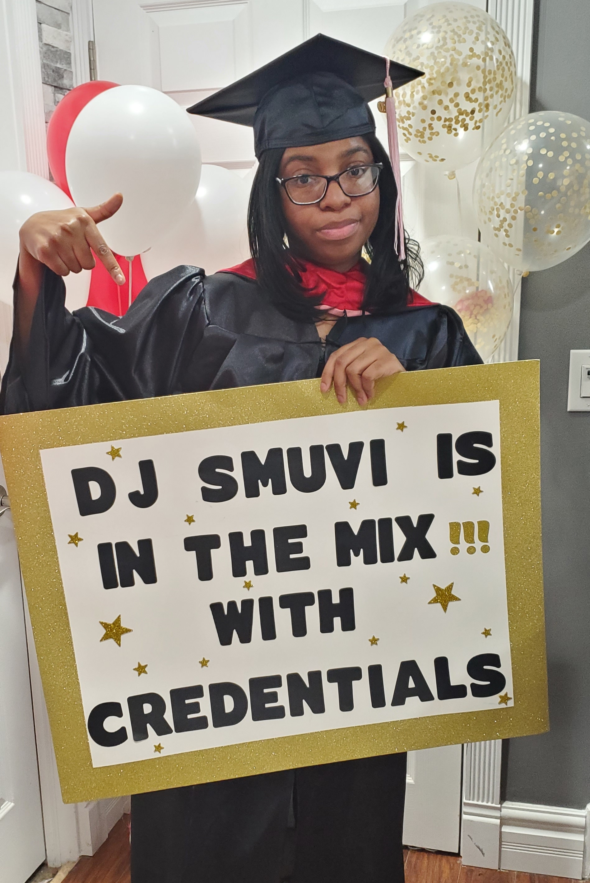 Gabrielle Davis holds up a sign that reads: DJ SMUVI IS IN THE MIX WITH CREDENTIALS.