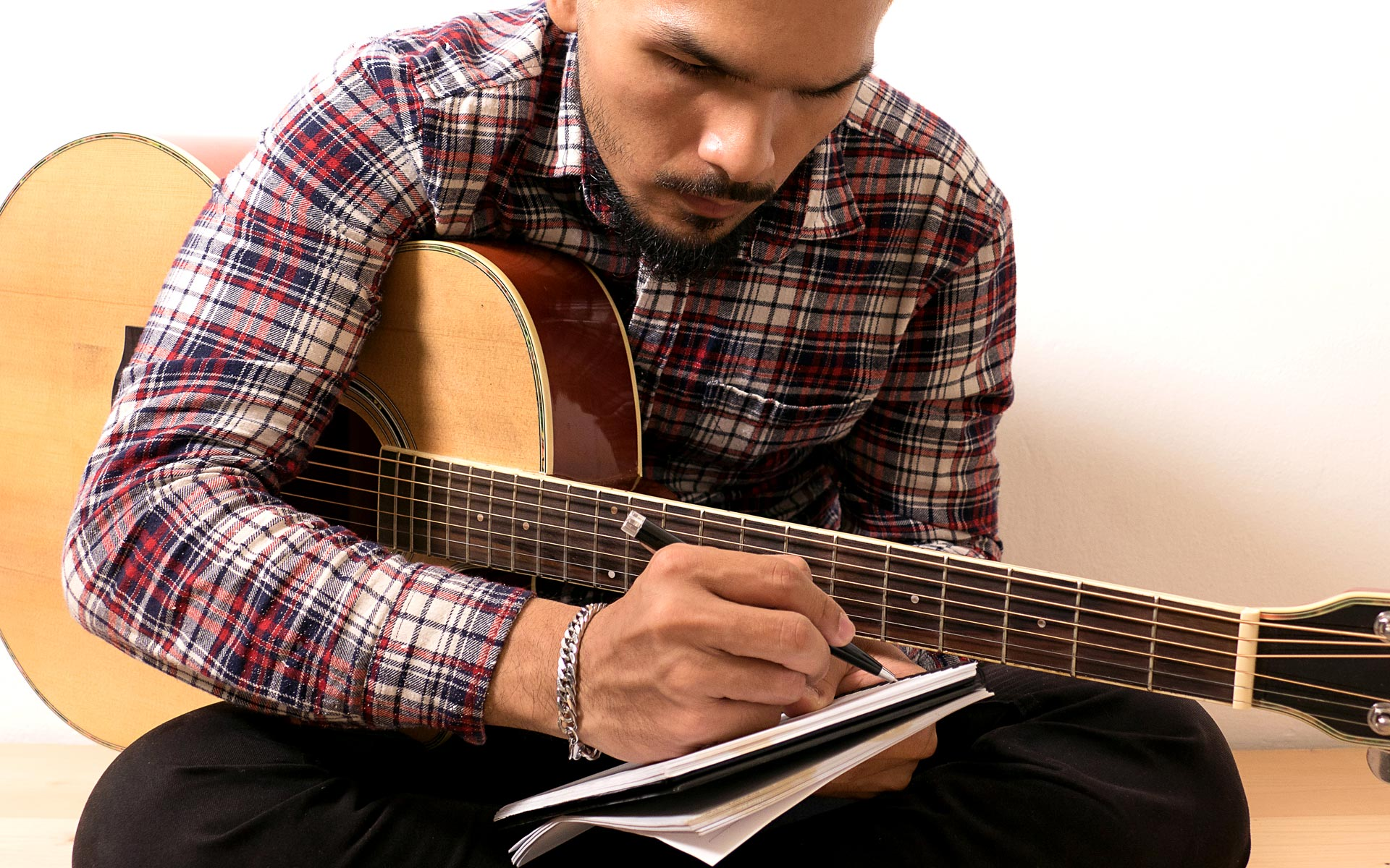 Man with a guitar writing a protest song.