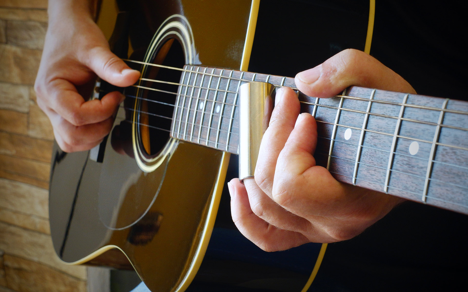 Acoustic blues guitar with a slide.