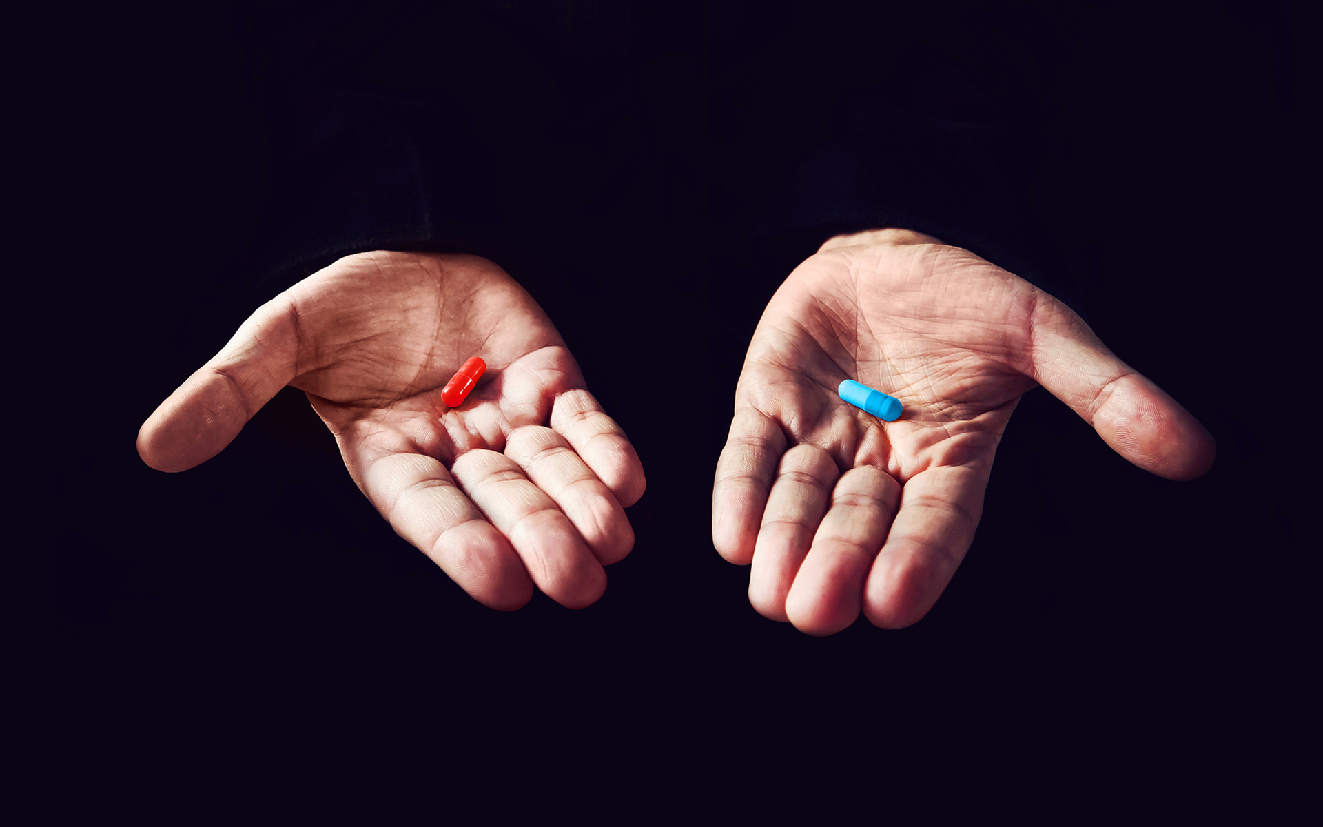 Two hands floating in a black background. The left hand with a red pill and the right hand with a blue pill.