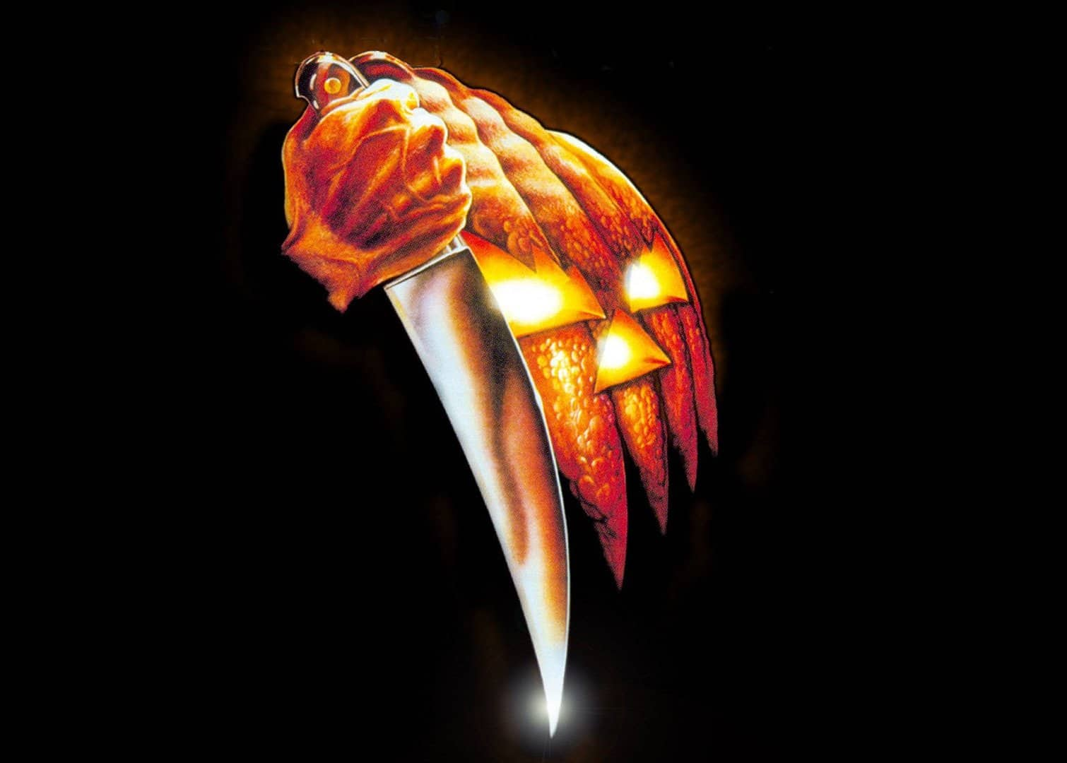 "The 1978 ""Halloween"" movie image of a jack-o'-lantern figure holding a knife."