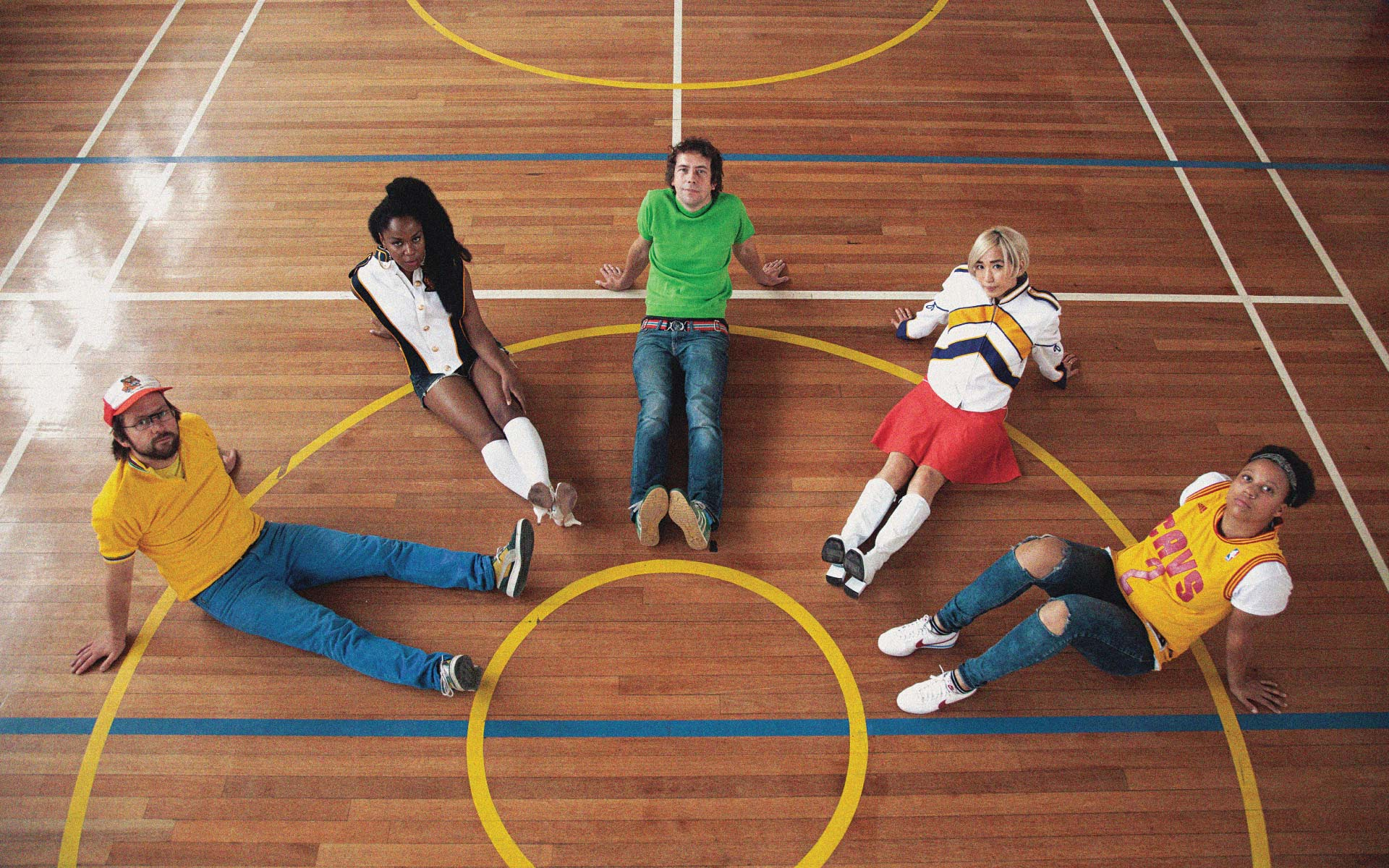The Go! Team are pictured, sitting in a circle on a basketball court.