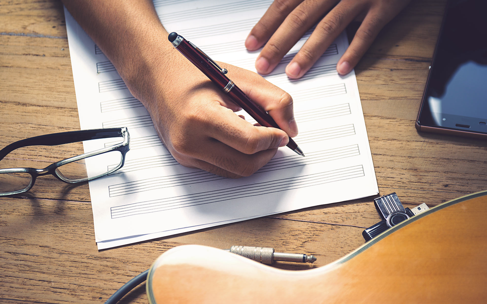 A musician writing on a piece of staff paper, with their glasses, guitar, and smart phone on the table.