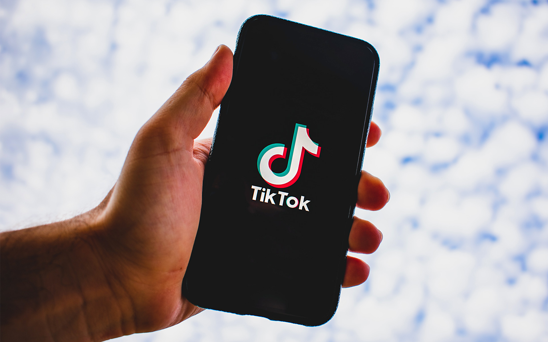 A hand holds a cell phone, featuring the TikTok logo on the screen, towards the clouded sky.