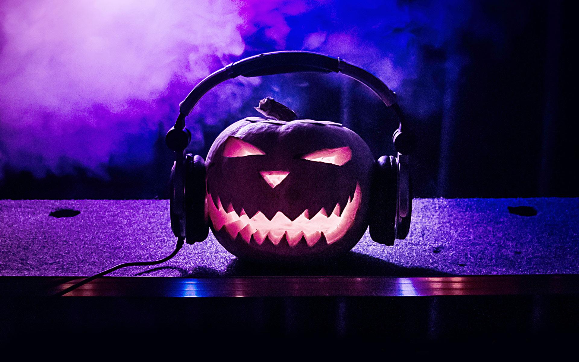 An illuminated jack o' lantern wearing headphones sitting on top of a soundboard surrounded by purple smoke.