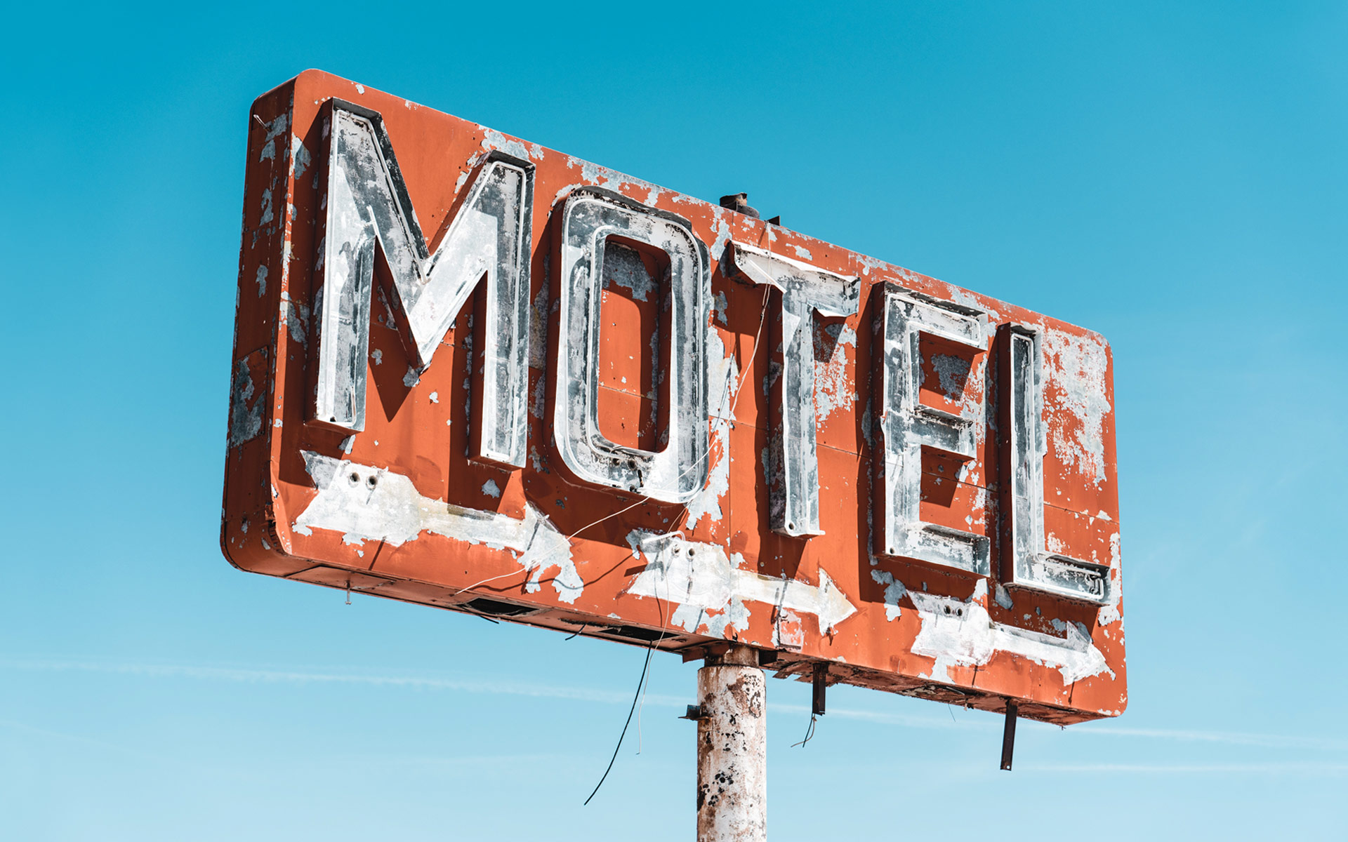 A rusty orange sign with white letters that read: MOTEL, against a blue sky.