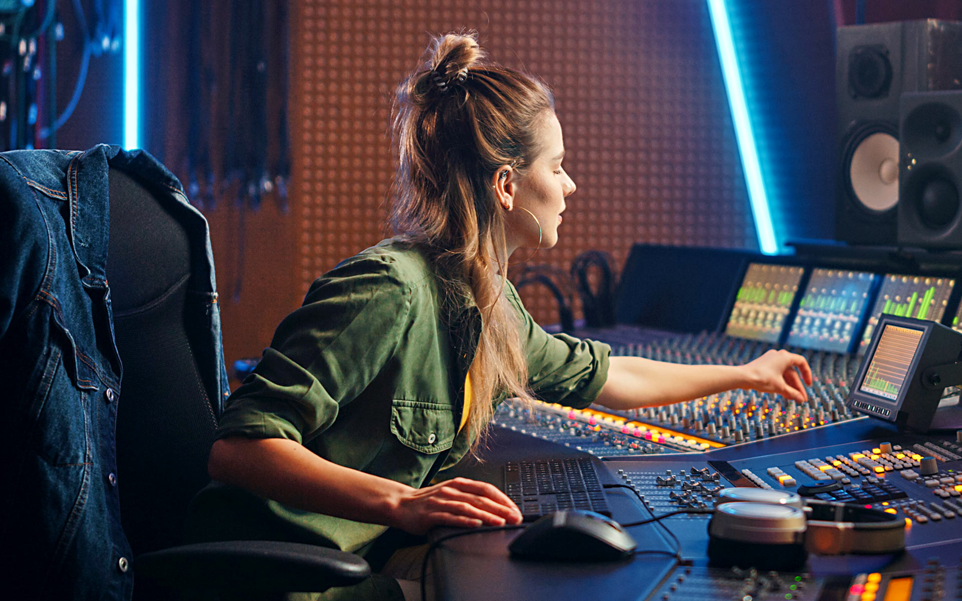 A music producer sitting at a sound board in a recording studio.