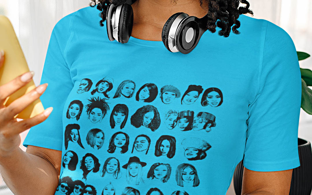 A person wearing a blue shirt featuring several faces of women rappers. The shirt is one of the suggested gifts for musicians and music lovers.