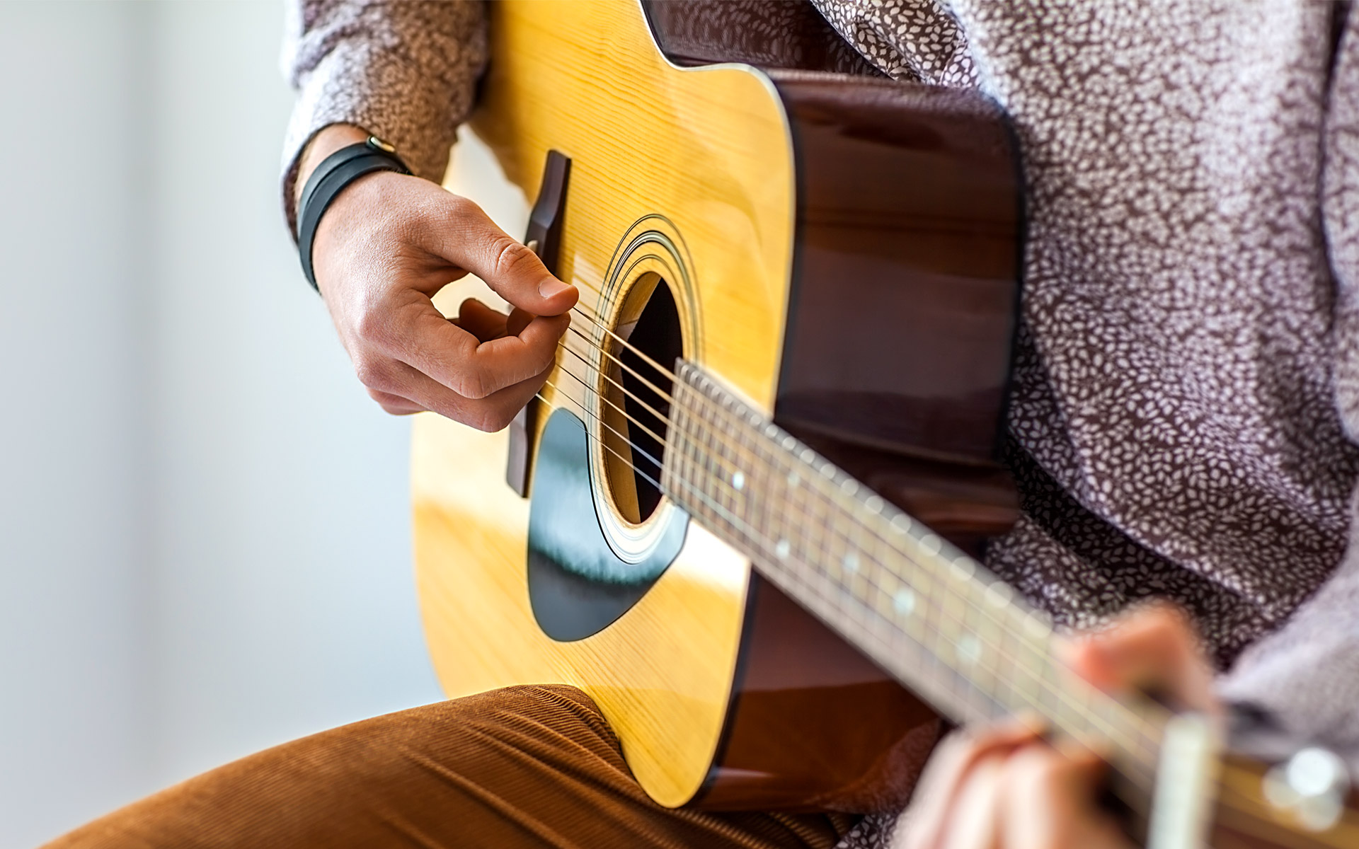 A person playing acoustic guitar.