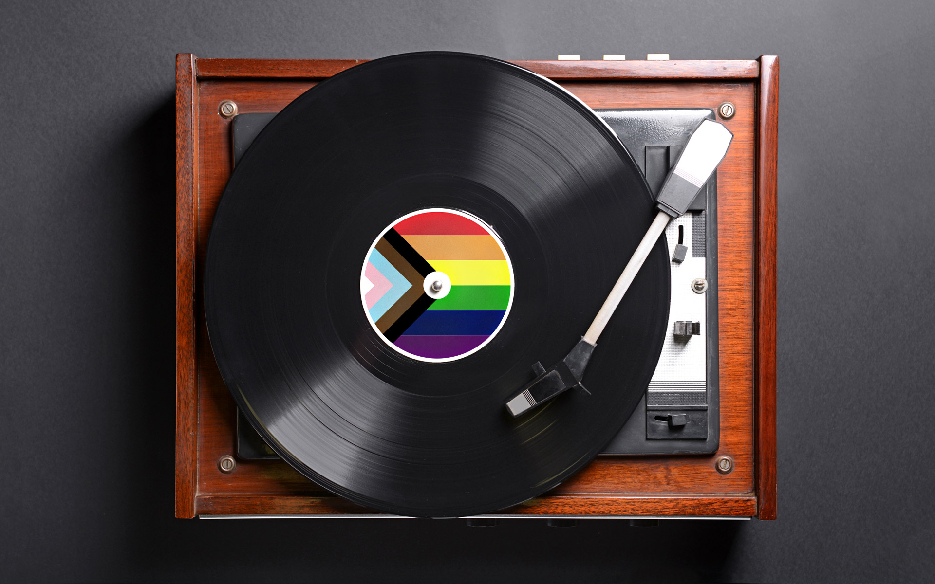 A wooden turn table that has a record on it featuring the LGBTQIA+ pride flag