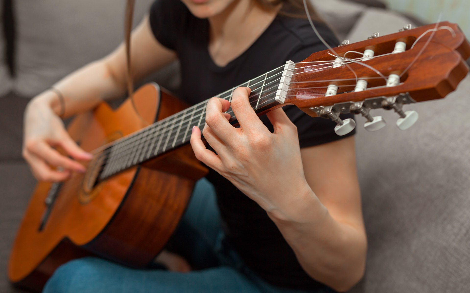 woman playing classical guitar on a couch