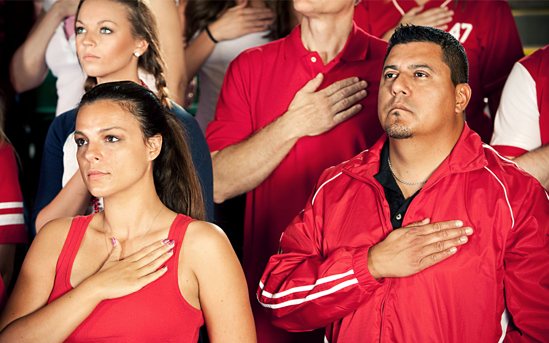 Attendees of a nondescript sporting event sing a nondescript national anthem for a nondescript country in this stock image.