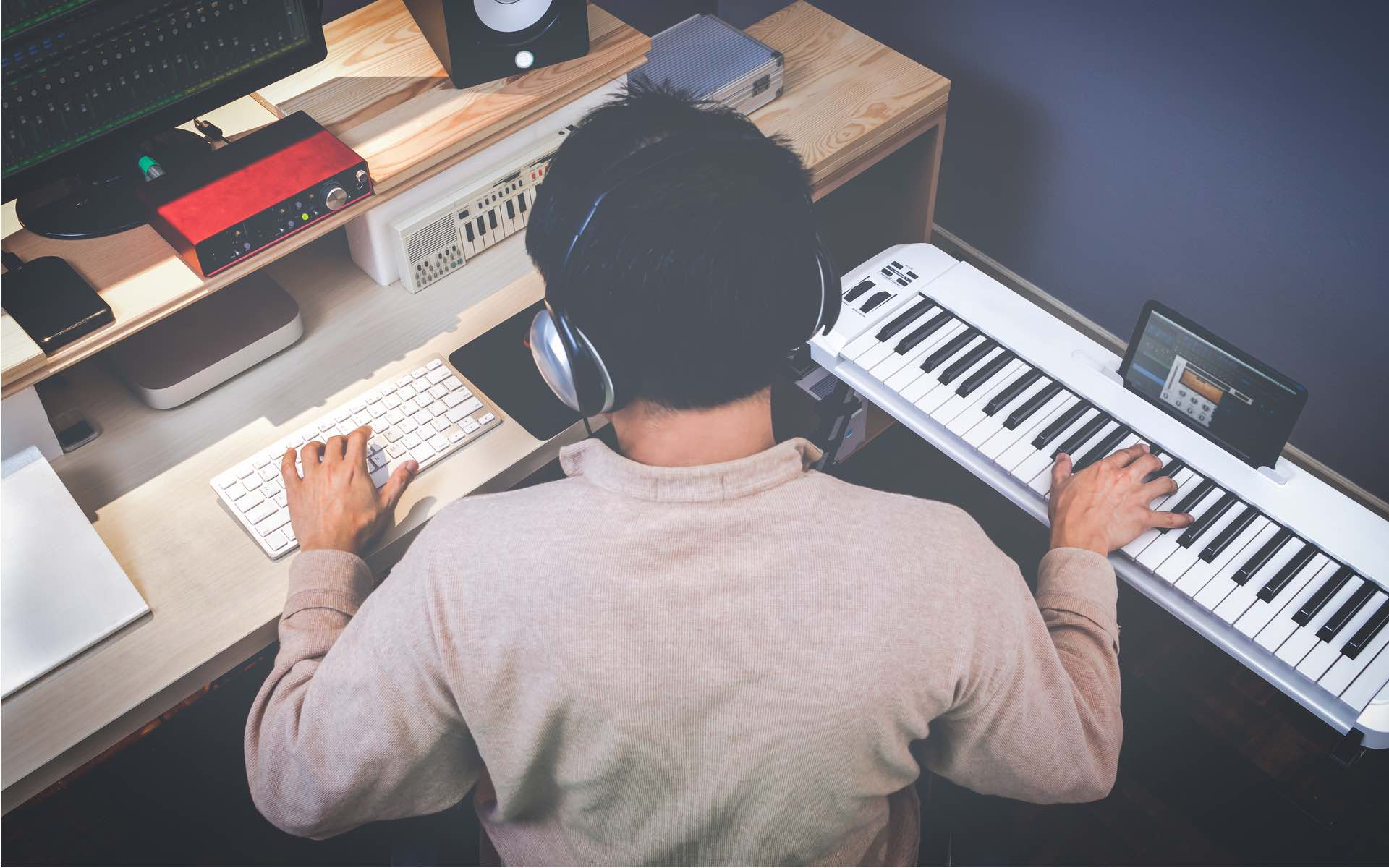 music composer working at their computer and keyboard